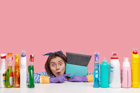 Indoor shot of stupefied Caucasian housemaid points aside, carries broom closely, demonstrates result of cleaning dirty room, uses different detergents, isolated over pink wall with free space above