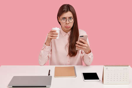 Upset brunette female office perfectionist has unhappy expression, drinks takeaway coffee, holds mobile phone, wears round spectacles, elegant shirt, likes everything is in proper order. Perfectionsim