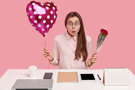 Photo of astonished beautiful lady surprised to recieve words of congratulation and present from partner, holds flowers and valentine, feels surprised sits at desktop with necessary suppiles for work.