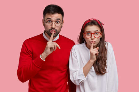 Young surprised couple make silence sign, stand closely to each other, keep index fingers on lips, demonstrate shush gesture, ask not tell secret, try be mute, isolated over pink studio wall. Be quiet