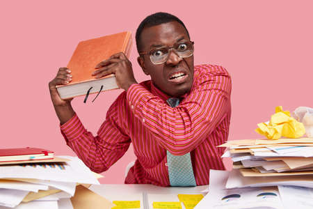 People, anger, threat concept. Irritated male teacher holds big encyclopedia, going to revenge with someone, feels annoyed with constant studying, wears pink shirt, has no spare time for rest