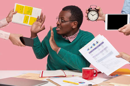 Oh no, not now. Stressed dark skinned man has much work in office, asked by many people at one time who remind about preparing business project, hold alarm clock, notepad with records, sits at desktop