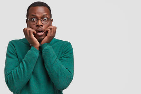 Nervous scared ethnic man with dark skin, keeps hands near mouth, feels worried, wears elegant sweater, isolated over white background with copy space for your advertisement or promotional text