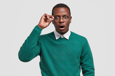 Surprised dark skinned male teacher keeps hand on rim of glasses, wears elegant white shirt and green sweater, says wow as sees incredible project of students, isolated over white background