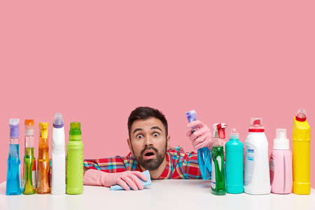 Isolated shot of bearded man has shocked expression, stares at you, holds spray, uses rag for cleaning, sees dirty window, sits at table isolated over pink background with blank space above.