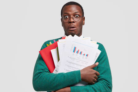 Photo of shocked dark skinned young man has surprised expression, carries papers with graphics, his notes, stupefied to notice many people on meeting, preapres for conversation with investors