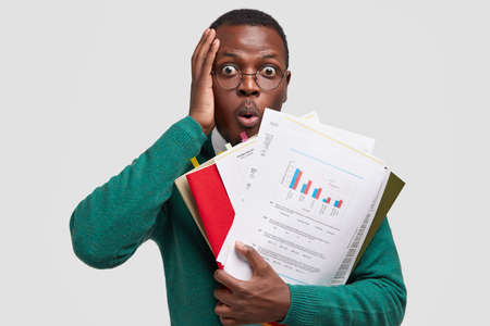 Headshot of puzzled African American man touches head, stares with bugged eyes, opens mouth from amazement, holds paper documents, has deadline for making task, isolated on white studio wall