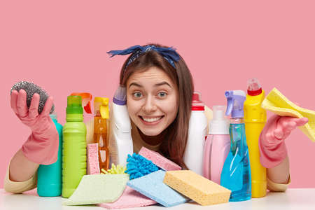 Pleased lady with European appearance, toothy smile wears headband, looks positively through detergents, carries mop for washing kitchen stove, models over pink background. Housekeeping concept