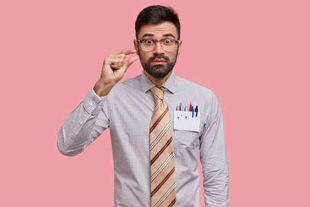 Photo of puzzled unshaven young man makes size gesture, demonstrates something tiny, wears formal shirt and long tie, has surpised expression, isolated over pink background. Omg, its too little