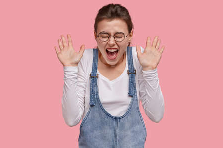 Pretty overjoyed lady exclaims loudly, shows palms, being greeted by best friend, wears white jumper and denim sarafan, squints face from pleasure, models over pink studio wall. Emotions concept