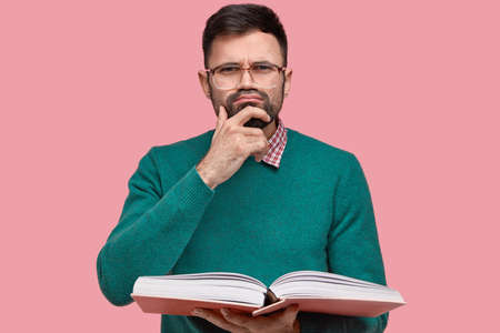 Horizontal shot of pensive bearded man has clever look, dark stubble, holds chin wears glasses for good vision, dressed in elegant clothes, carries opened textbook, contemplates information. Banco de Imagens