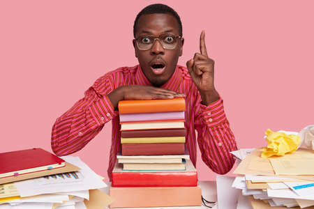 Stunned businessman with dark skin, keeps index finger up, opens mouth in amazement, dressed in formal shirt, gets good idea for developing startup, keeps hand on pile of books, busy working.
