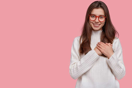 Kind tender girl presses hands to heart in thankful and touched gesture, has pleasant smile, wears white jumper, poses against pink background with copy space for your text. Body language concept