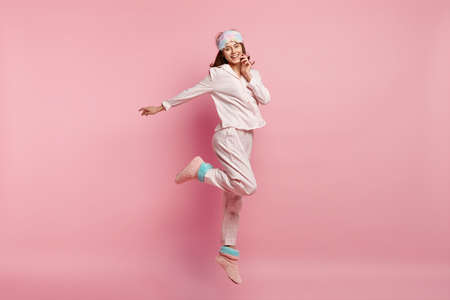 Indoor shot of overjoyed European woman raises leg, spreads hand, wears casual pyjamas and eyemask, smiles happily, isolated over pink background, enjoys bed time and good rest during weekend Imagens