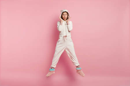 Photo of surprised young woman with eyes popped out, wears warm kigurumi costume, expresses disbelief, isolated over pink background, stare in bewilderment. People, bedding and stupor concept
