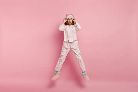 Isolated shot of astonished European woman stares with widely opened eyes, keeps hands near eyemask, dressed in nightclothes, wears domestic boots, jumps high, isolated over pink background.