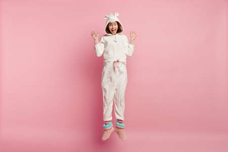 Overemotive young European woman raises palms, screams with happiness, wears warm kigurumi pyjamas, casual domestic slippers, isolated over pink background. Good morning concept and emotions.