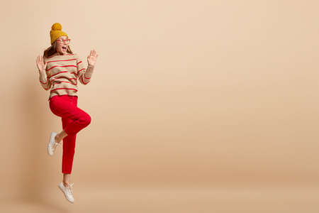 Studio shot of surprised woman with overjoyed expression, wears yellow hat, casual jumper and red trousers, jumps high, isolated over beige background with copy space for your promotional content