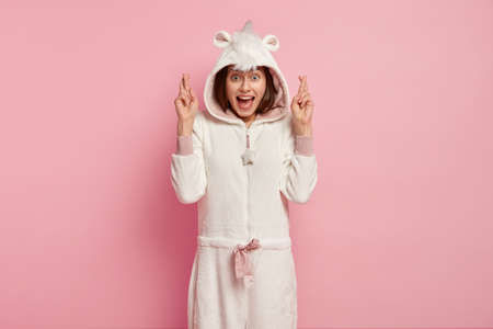 Indoor shot of happy European woman crosses figers for good luck, wears domestic funny kigurumi costume, poses against pink background, believes dreams come true. People and bed time concept