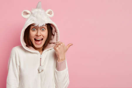 Happy Caucasian woman with pleased expression, wears unicorn costume, indicates with thumb aside, shows direction to shop of nightwear, isolated over pink background. Home and comfort concept