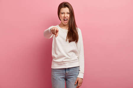 Strict dissatisfied woman points angrily directly at camera, exclaims with annoyance, frowns face in discontent, wears casual clothes, blames you, isolated over pink background, looks outraged