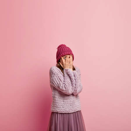Beautiful shocked woman covers face with palms, peeks through fingers, dressed in stylish hat, sweater and skirt, hides from someone, sees something horrified, isolated over pink wall with empty space Archivio Fotografico