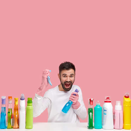 Image of emotive man with thick stubble, holds bottle of detergent and sponge, exclaims loudly, wears rubber protective gloves, isolated on pink wall with blank space above for your promotion