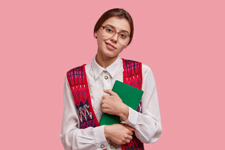 Photo of pleasant looking European female geek in big square spectacles, old fashionable blouse, carries notepad, looks with little smile at camera, satisfied with something, isolated on pink wall