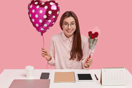 Glad dark haired woman has joyful expression, feels pleased to recieve present, carries valentine and red roses, has different objects neatly arranged at desk, isolated over pink background.