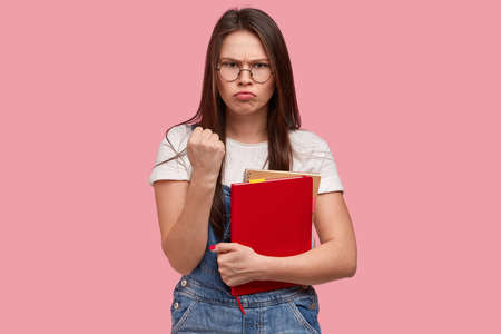 Discontent angry Asian young woman shows fist, feels annoyed, looks with gloomy expression, warns about revenge, carries red notepad, dressed in casual clothes, models against pink background.