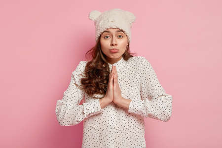Pretty woman with pleading pity expression, keeps palms pressed together, asks for help, dressed in polka dot shirt, warm hat in form of bear isolated over pink background. Please dont forget about me