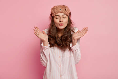Studio shot of affectionate pleasant looking young woman spreads palms and pouts lips for kiss, wears sleep mask and domestic night costume, isolated over pink background. Home and rest concept