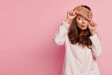 Indoor shot of funny young European woman wears eyemask, pyjamas, looks away, poses against pink background with copy space for your promotional content or advertisement. People and rest concept