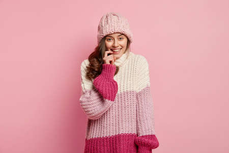 Waist up shot of good looking young woman with dark hair, keeps fore finger near lips, has toothy smile, wears casual hat and oversized pullover, ready for walk in winter, isolated on pink wall