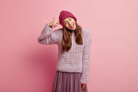 Comic teenager foolishes indoor, shoots herself in temple, tilts head, wears headgear, loose sweater and skirt, poses against pink background, has fun in winter. Suicide gesture. Season concept