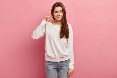 Photo of displeased dark haired young woman shows tiny small object, demonstrates ammount of attention she needs, dressed in casual outfit, isolated over pink background. People and size concept.