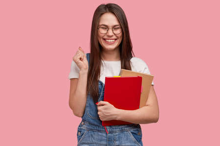 Happy brunette lady clenches teeth and fist, wears casual clothes, holds notepad for writing notes during lecture, smiles broadly at camera, shows white teeth, models against pink background