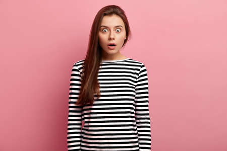Astonished attractive woman with eyes popped out, has long hair, amazed expression, afraids of something, wears striped clothes, isolated over pink studio background, finds out about catastrophy Banque d'images