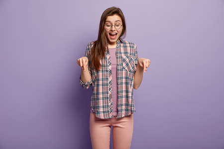 Pleased delighted Caucasian woman with dark straight hair, wears optical glasses, smiles happily, demonstrates wonderful thing on floor, poses over purple background. People and advertisement