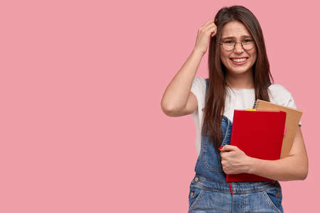 Indoor shot of puzzled woman scratches head, tries fnd answer on question, uses spiral notepad for writing notes, wears optical round glasses and denim overalls isolated over pink wall with free space