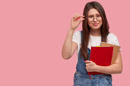 Brunette dissatisfied woman shows little sign, measures something very tiny, demonstrates how much she knows material for exam, holds two notepads, wears jean overalls, isolated on pink wall