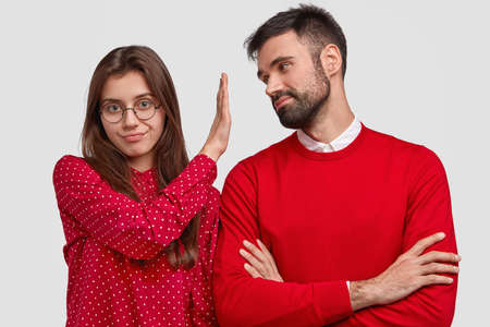 Angry European woman in red blouse makes refusal gesture, keeps palm in front of boyfriends face, doesnt want to listen his apologize, can not trust after betrayal. People and relationship concept