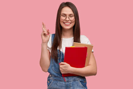 College student with happy look, crosses fingers for good luck on exam, holds notebook for writing records, dressed in denim overalls, models against pink background, enjoys tuition and studying