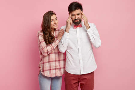 Clever student with stubble keeps fore fingers on temples, concentrates on something, dressed in elegant clothes, cheerful woman keeps hand on his shoulder, helps to recall information, pose indoor