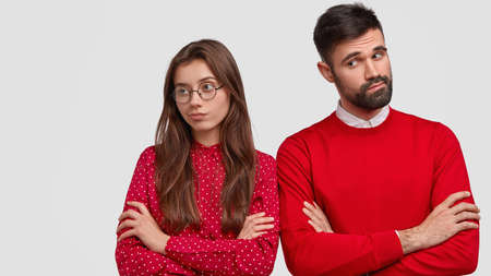 Isolated shot of attractive woman in red sweater keeps arms folded, turns away from boyfriend, sort out relationships, feel displeased, isolated over white background. Disagreement and relations Foto de archivo