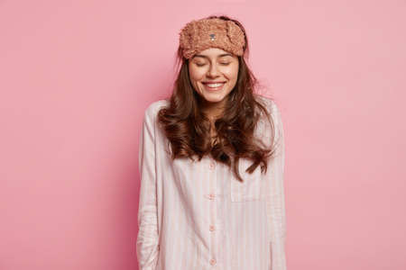 Horizontal shot of pleased young European woman closes eyes and smiles gently, wakes up in good mood after seeing pleasant dreams at night, dressed in casual domestic clothes, funny eyemask on head
