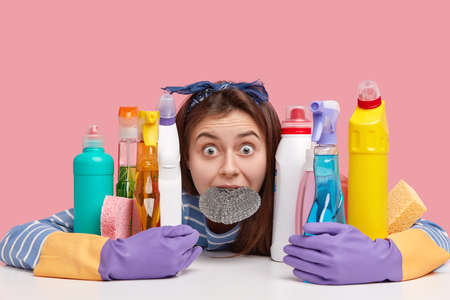 Headshot of stupefied dark haired with widely opened eyes, keeps sponge in mouth, foolishes after long day working, embraces bottles with cleaning supplies, sits at table against pink background