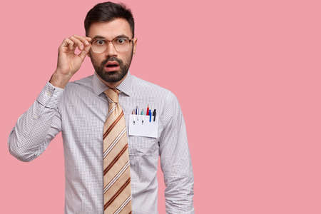 Indoor shot of stupefied unshaven male arhitect keeps hand on frame of spectacles, hears shocking news, wears formal clothes, stands against pink studio wall with copy space for your advertisement