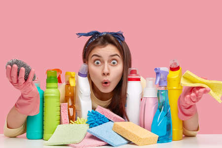 Photo of overwhelmed beautiful young woman keeps eyes widely opened, loosk with surprisement and hesitation, holds rag or sponge, finds out about house chores, isolated over pink background.