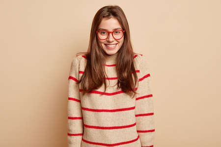 Positive dark haired woman with straight hair, toothy smile, dressed in casual sweater, looks directly at camera, expresses happiness, isolated over beige background. People and emotions concept Stockfoto